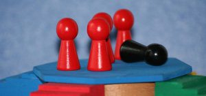 Several red wooden pieces representing people standing up, while a black piece is laying on the floor